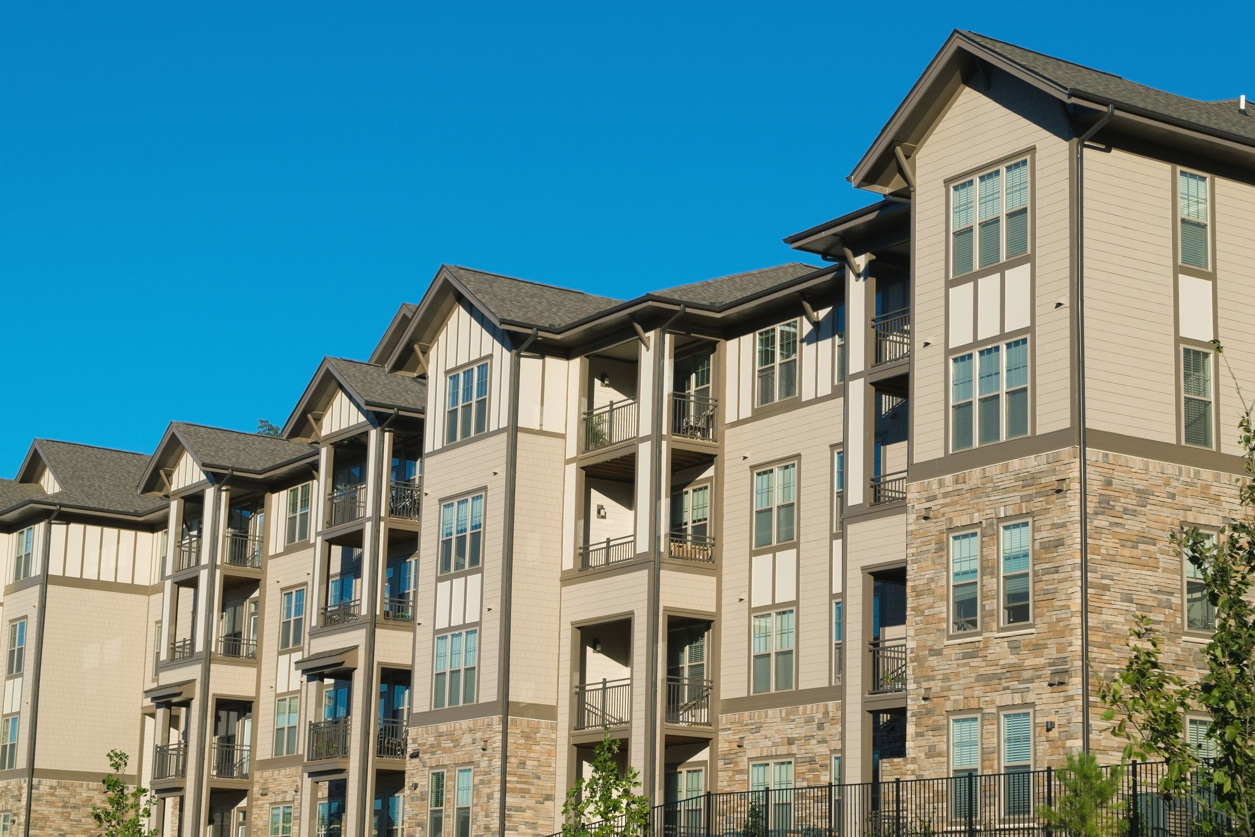 Townhouse Complex with tan colored commercial composite siding blue sky above